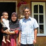 Bang Hem and Dae, holding Farit, in Ban Talae Nok village on Thailand's Andaman coast