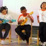 Thai children performe music performance with volunteers